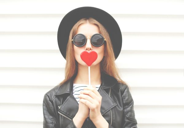 Millennial girl with heart-shaped lollipop