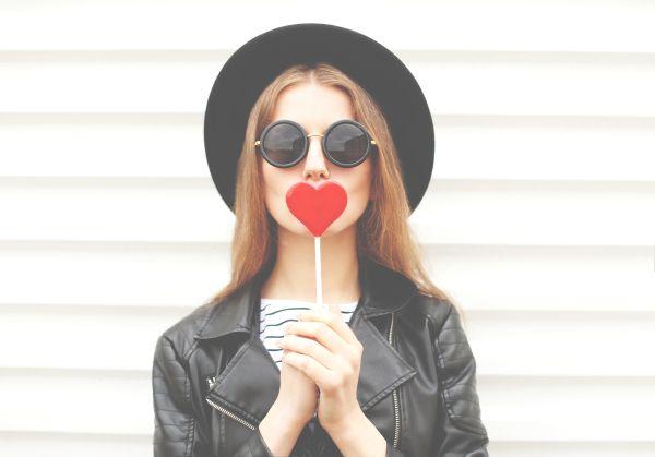 Millennial girl with heart-shaped lollipop