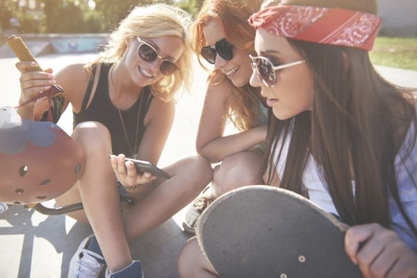 Group of millennial women streaming a video on phone